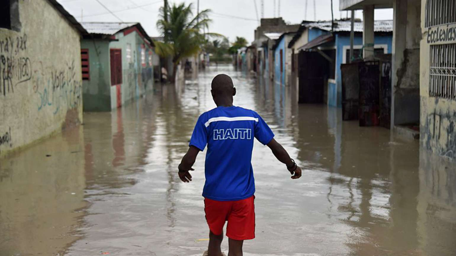 A child walks through flooded streets in Haiti