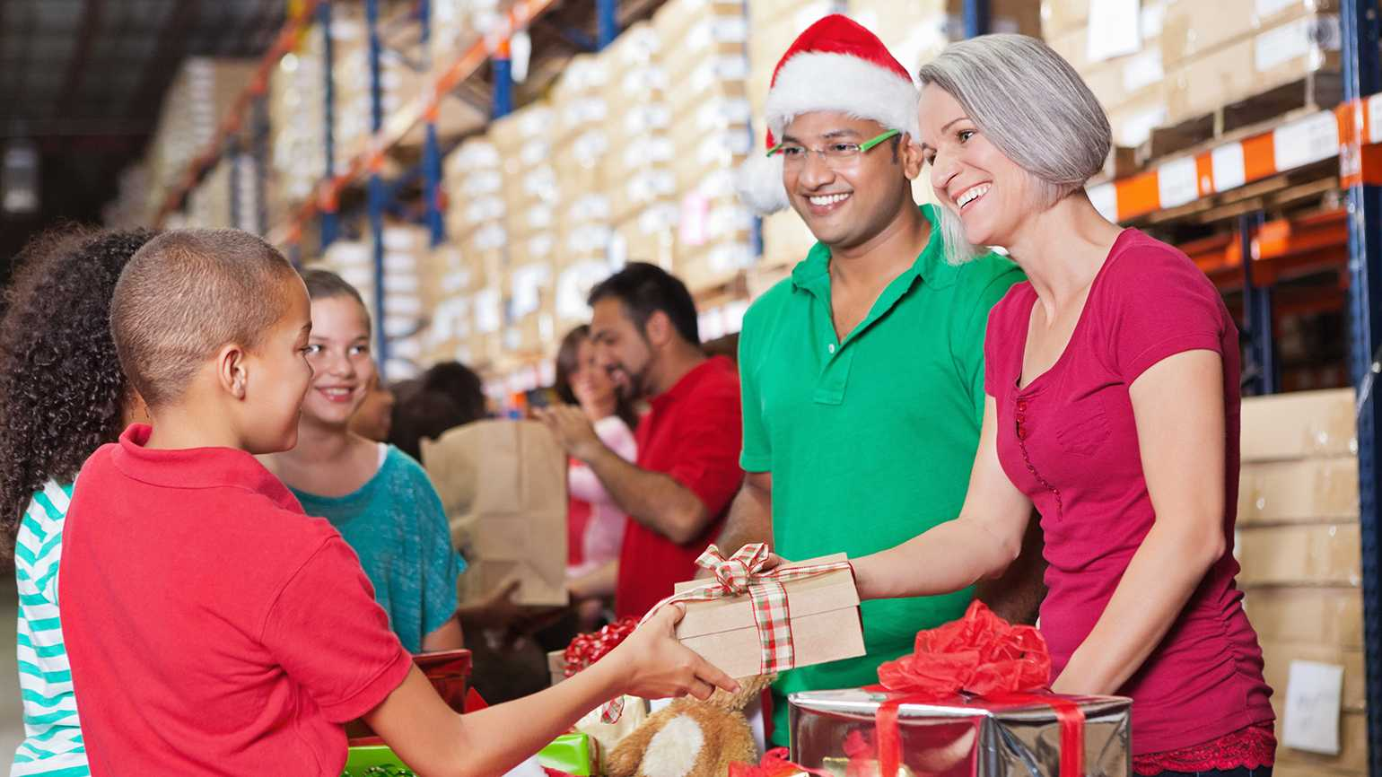 Charity volunteers give wrapped gifts to children
