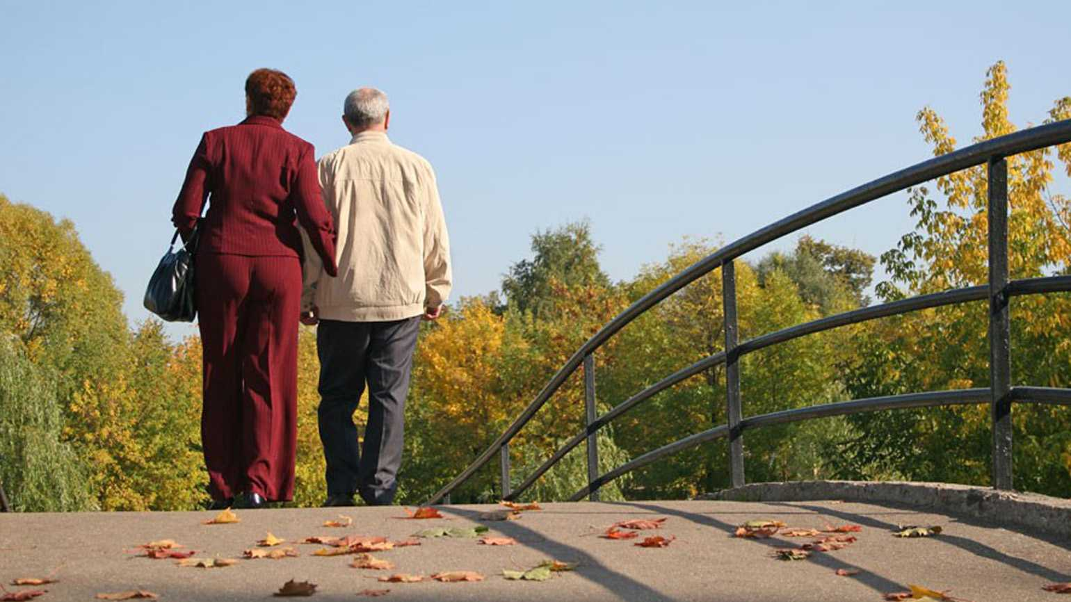 A senior couple walking across a bridge during the Autumn season.