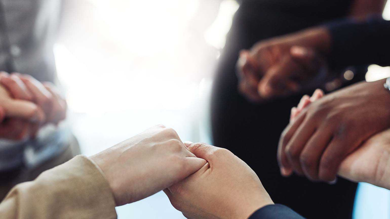 Hands holding each other in a circle; GETTY IMAGES/ISTOCKPHOTO