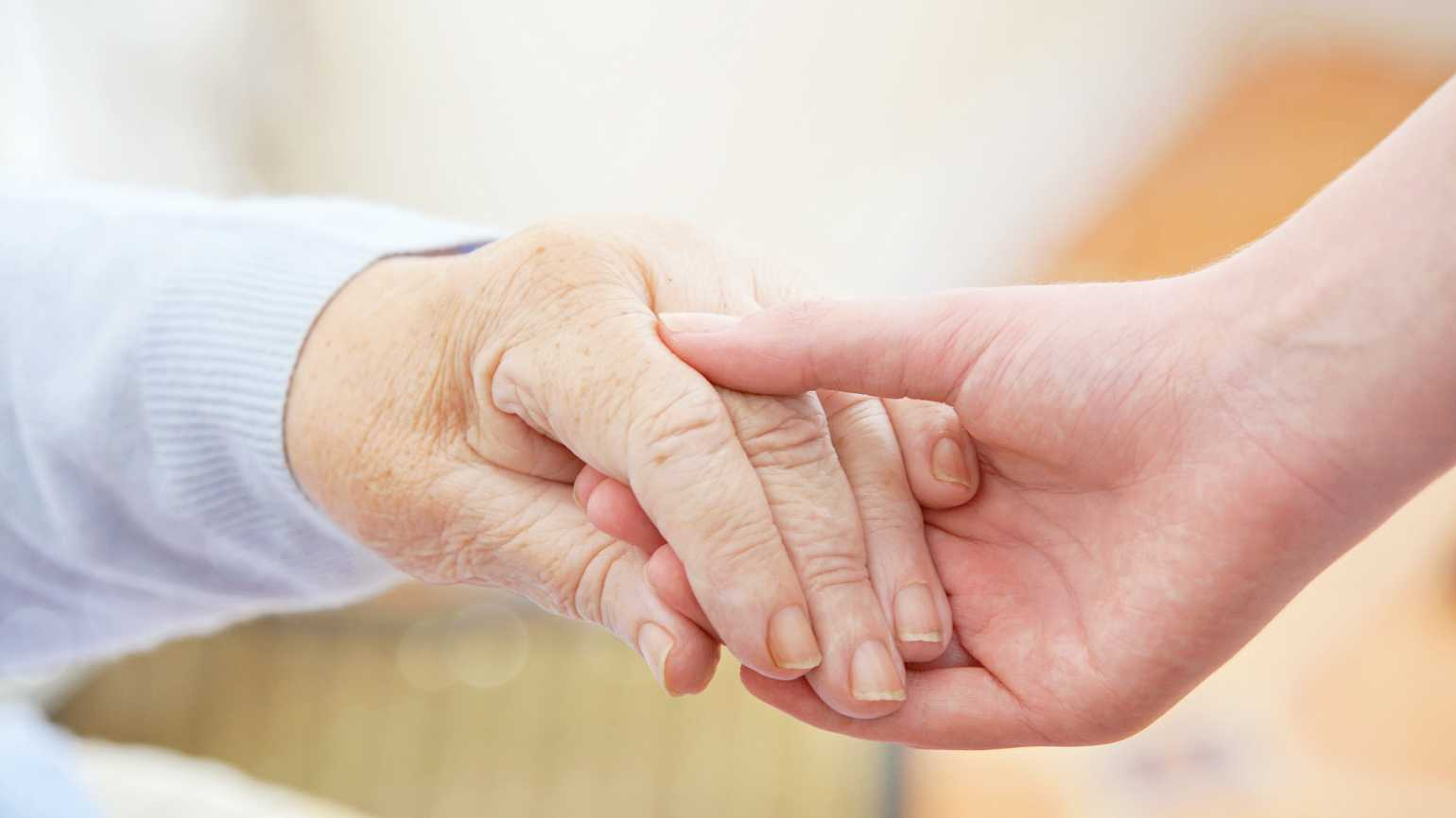 A close up of an older and younger patient holding each other's hands for help.