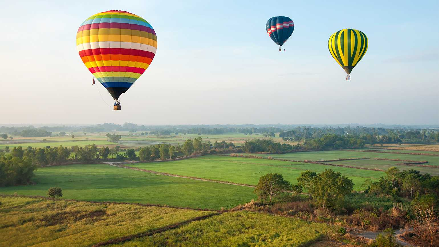 Hot air balloons float over a scenic countryside