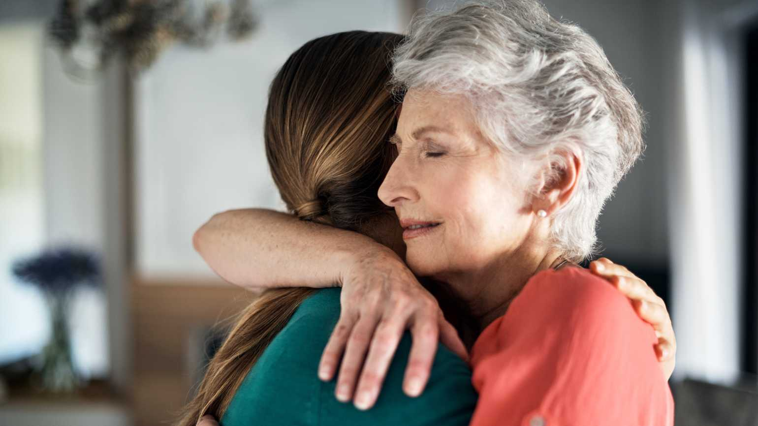 A caregiver hugs an aging loved one.