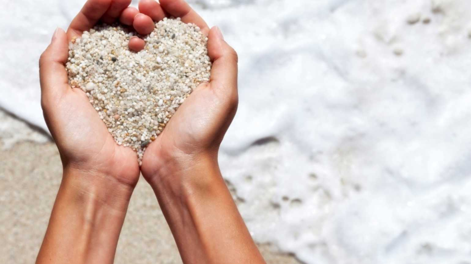 Hands holding sand in a heart-shape to symbolize Jesus' love for us