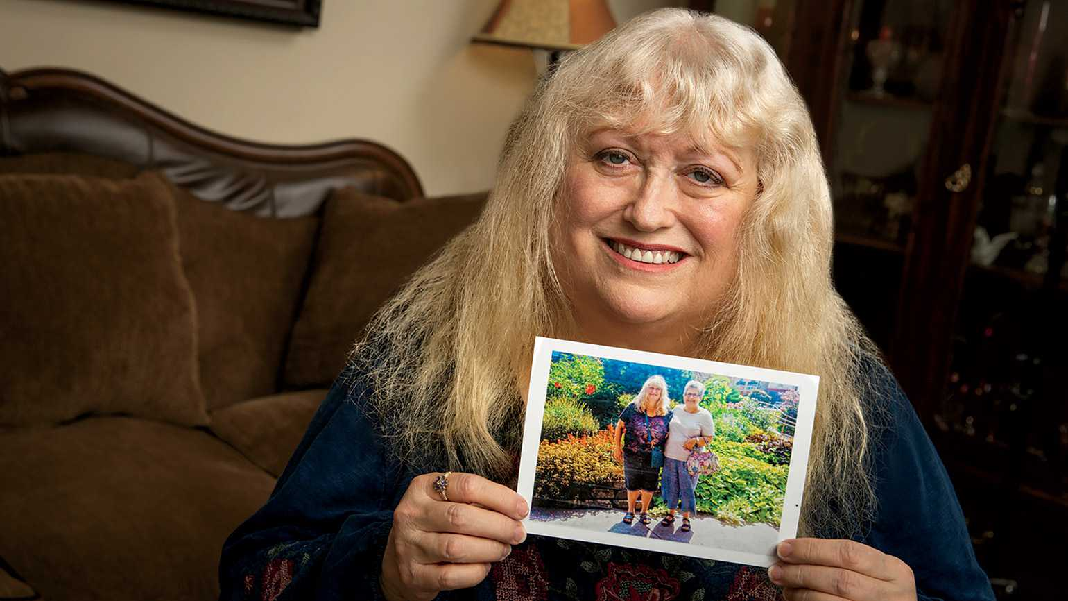Kristy Dewberry holds a photo of herself and Carol; photo by Shevaun Williams