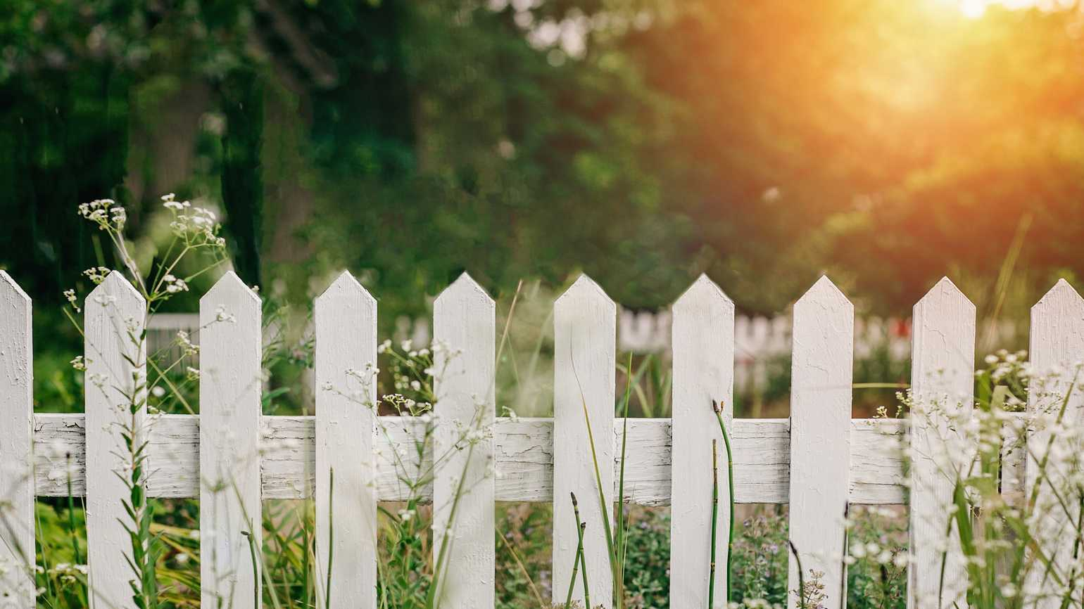 A country fence with sunshine peeking in.