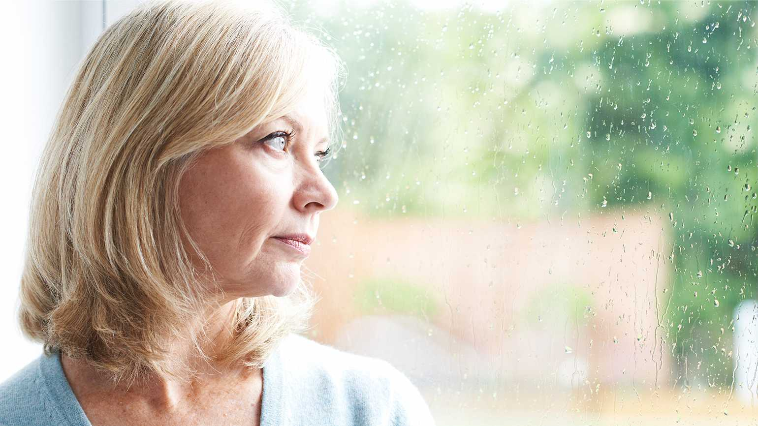 A depressed senior woman gazes out the window
