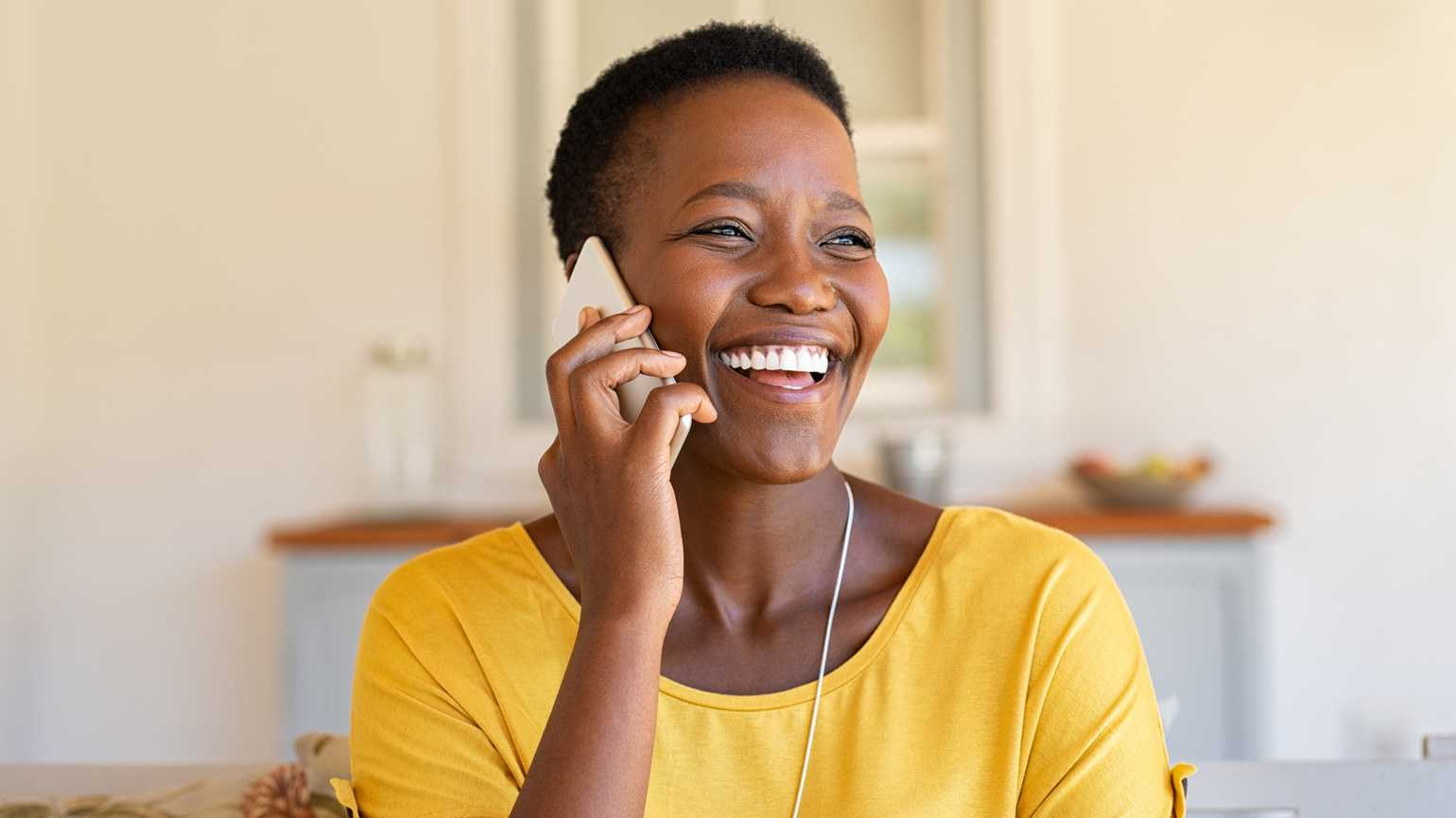 A woman happily talking on the phone.