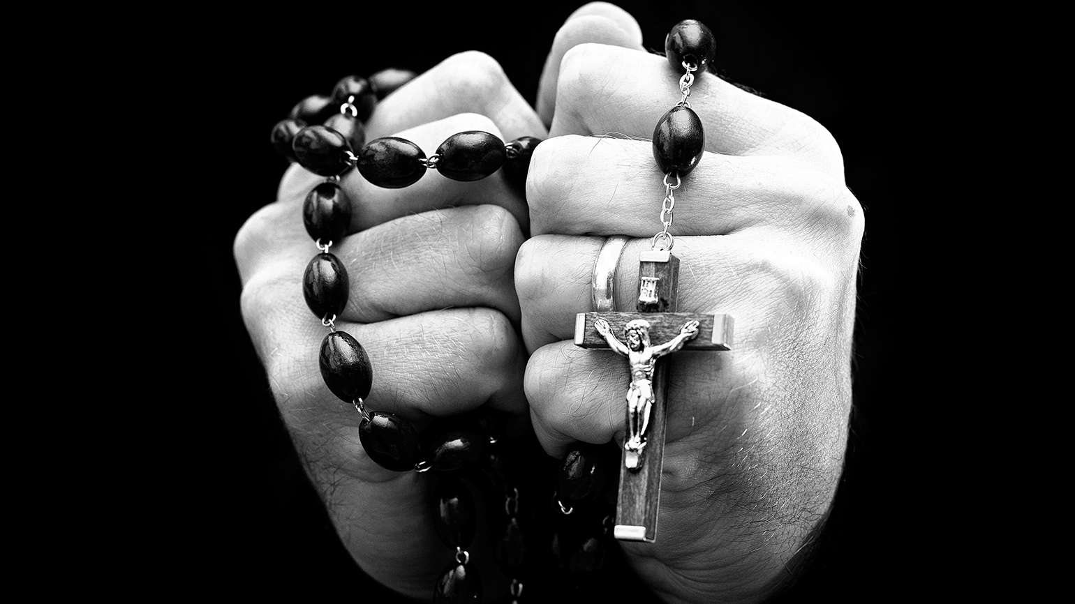 A man's hands clasp a rosary
