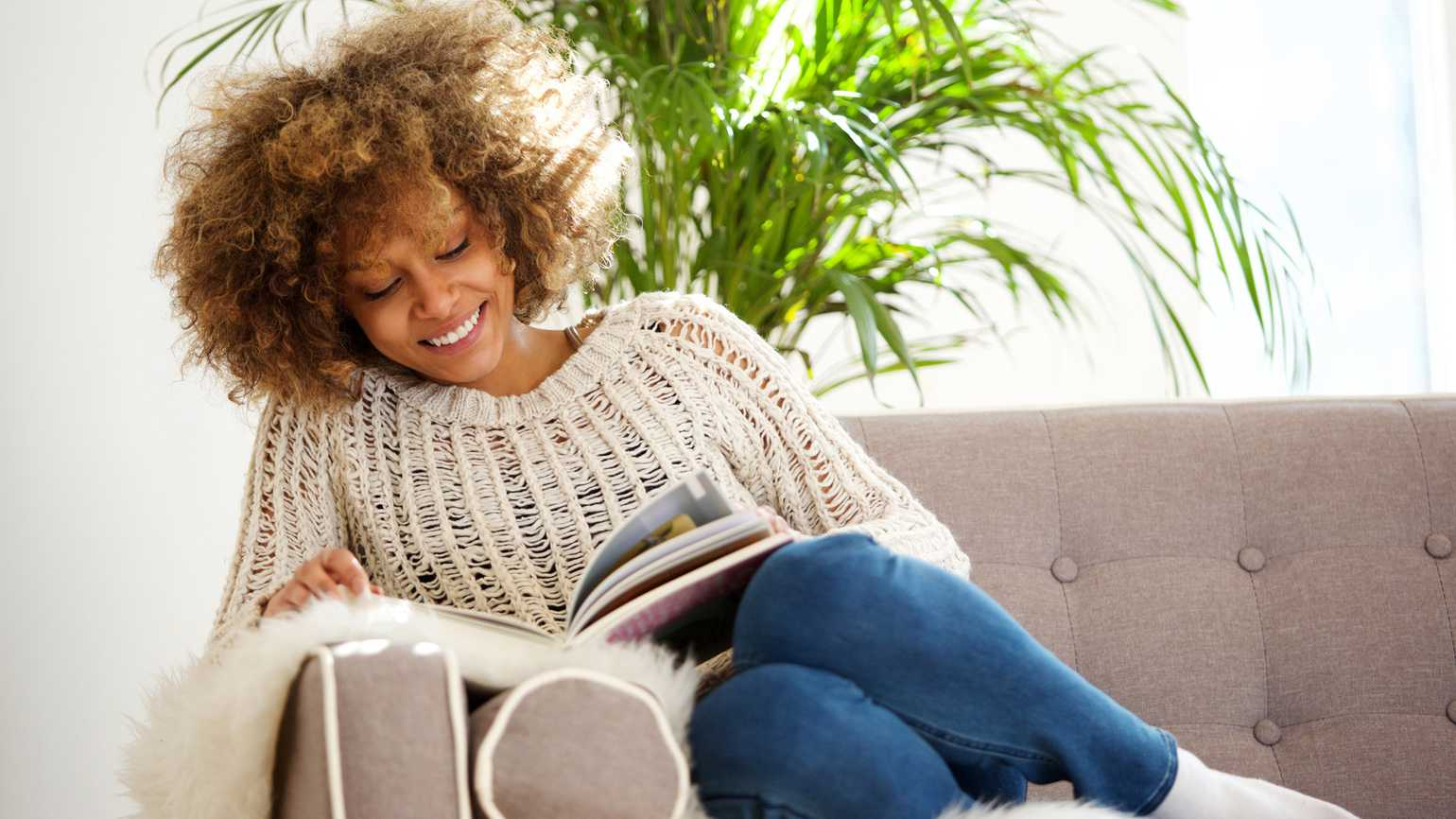 A woman on a sofa reading a book.