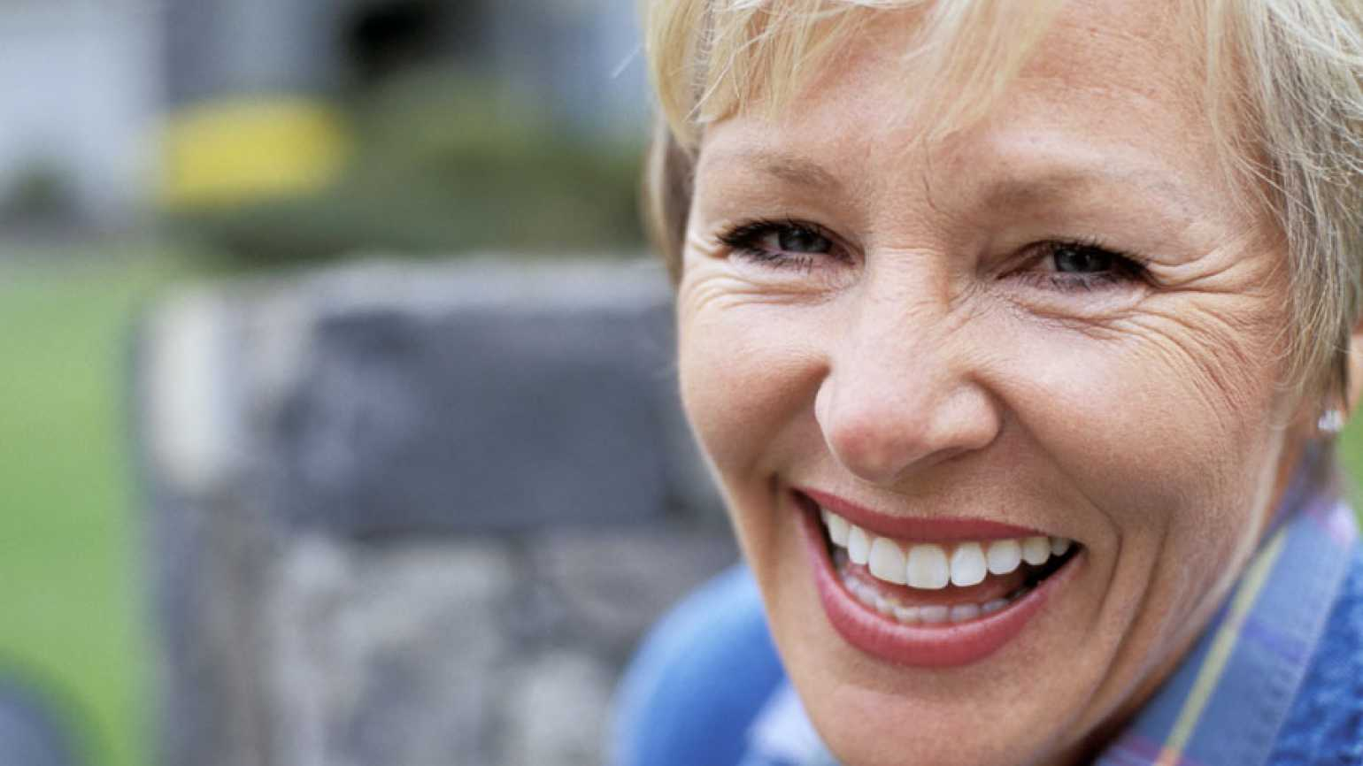 A happy mature woman smiles broadly