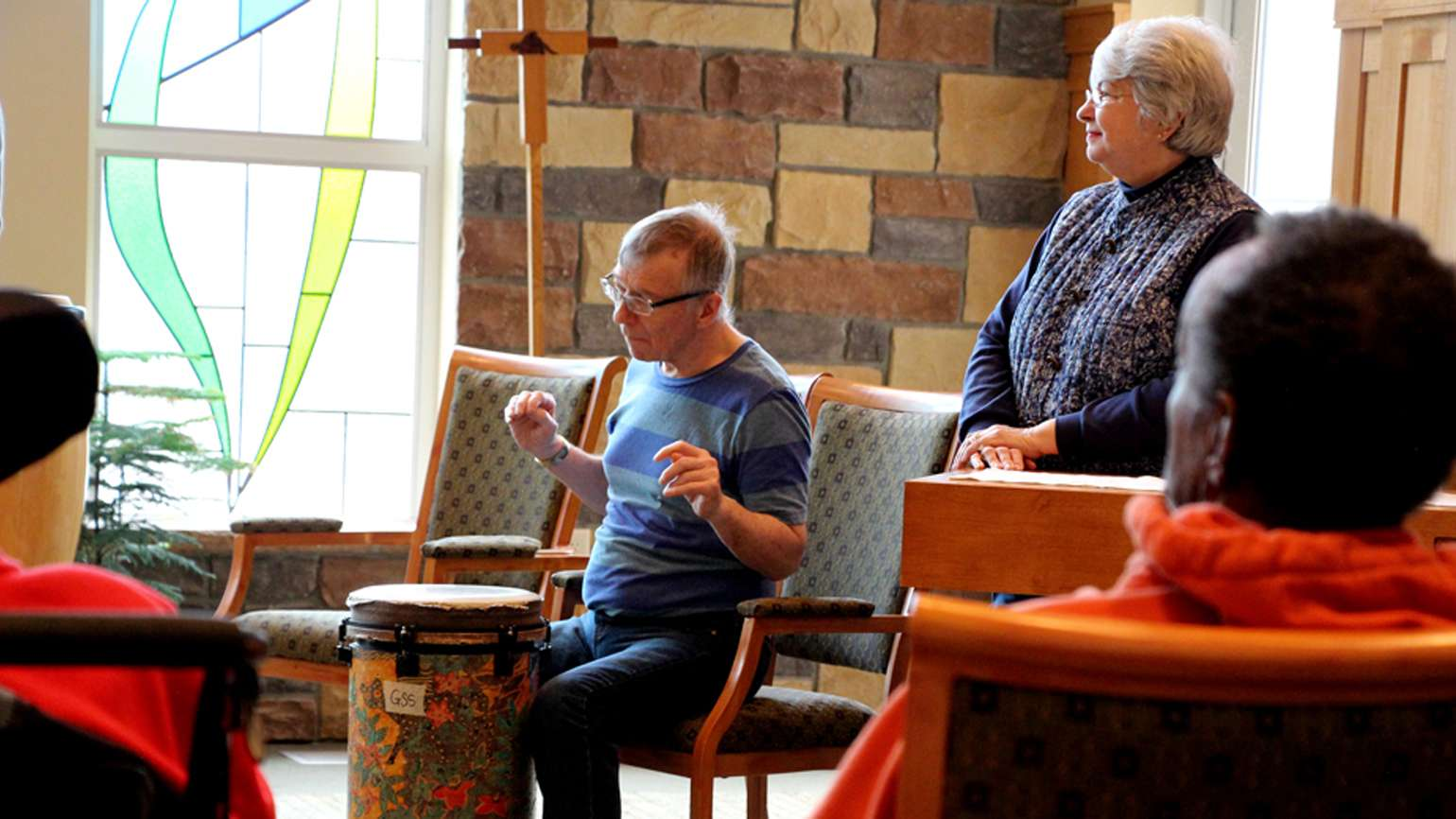 Fred drumming on an African drum with his wife, Jeanette standing by his side.