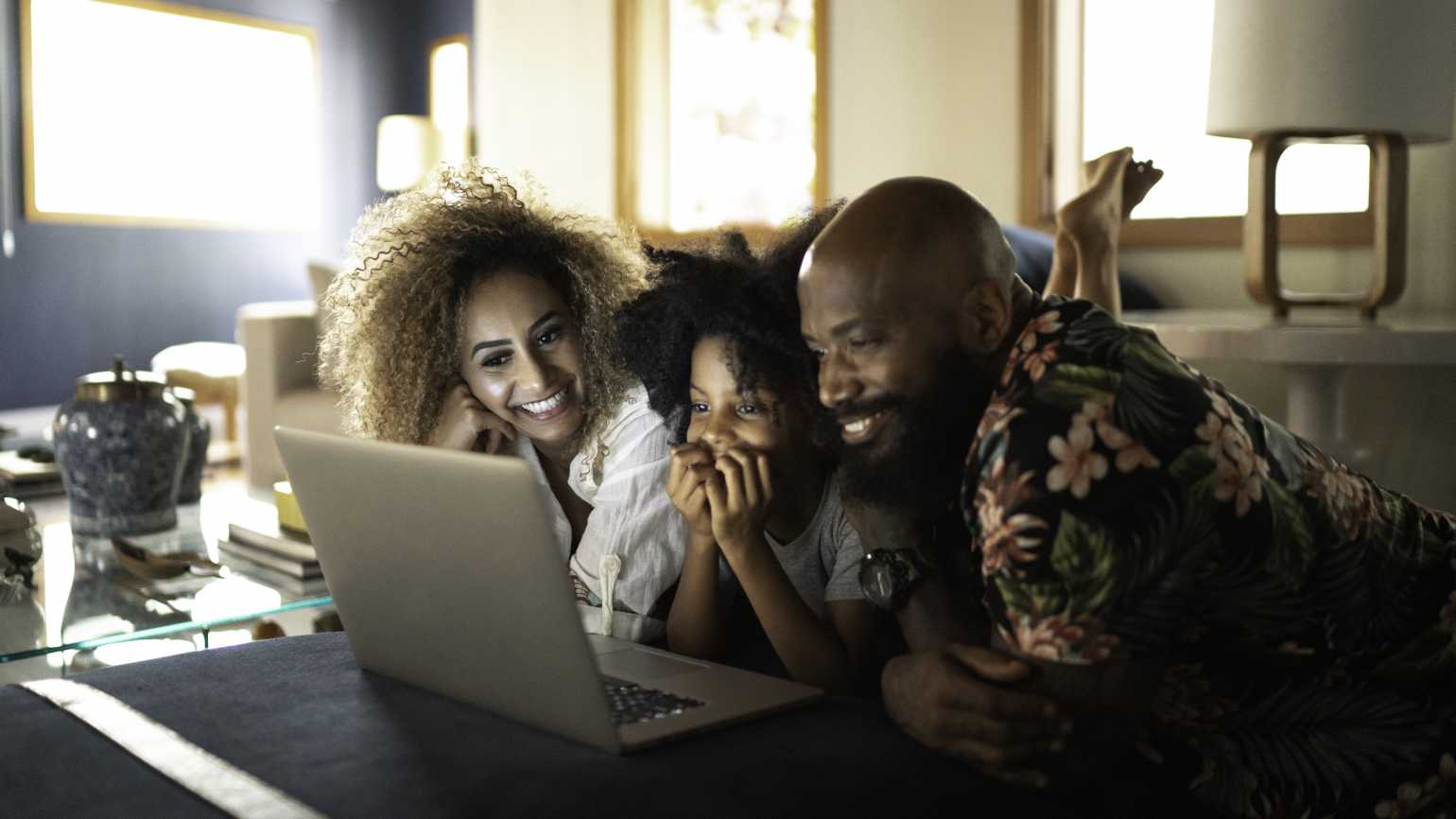 Family smiling at computer screen