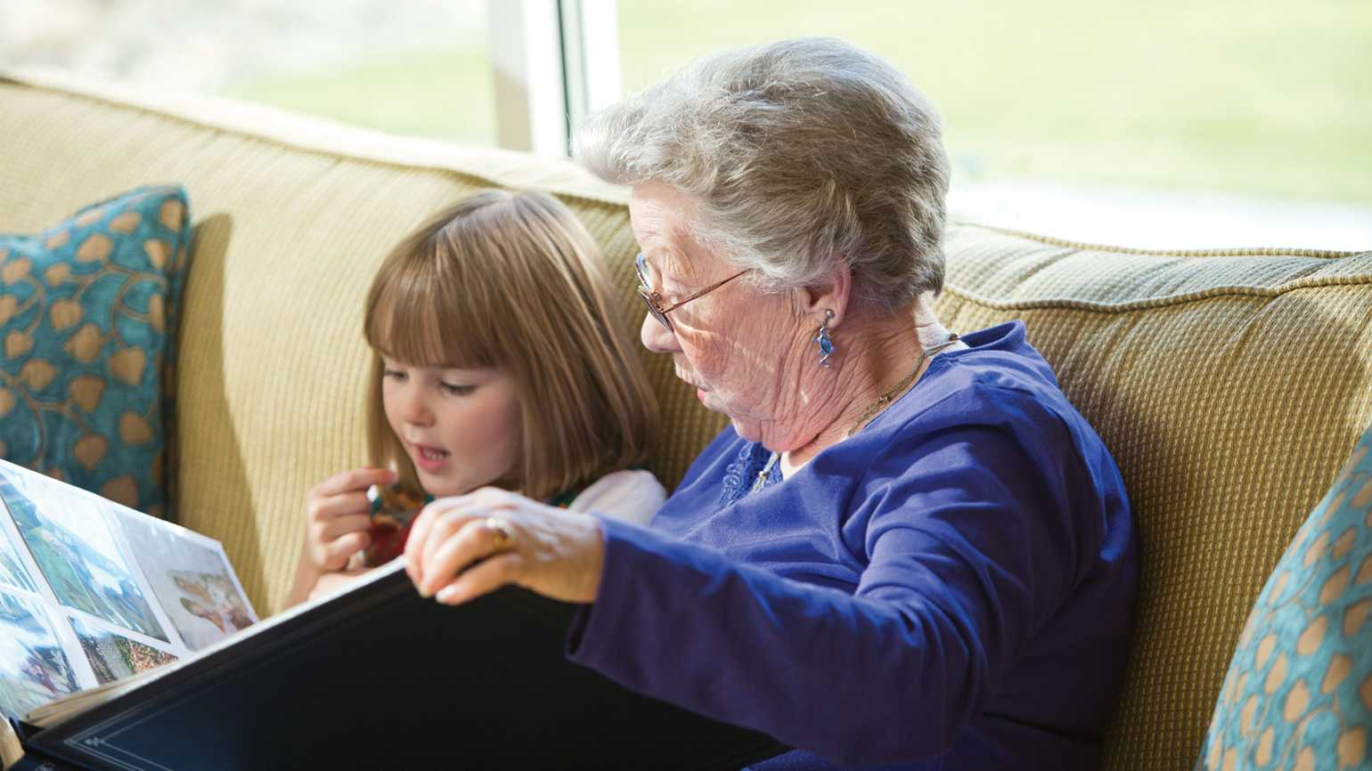 A senior citizen woman reads to one of the preschoolers.