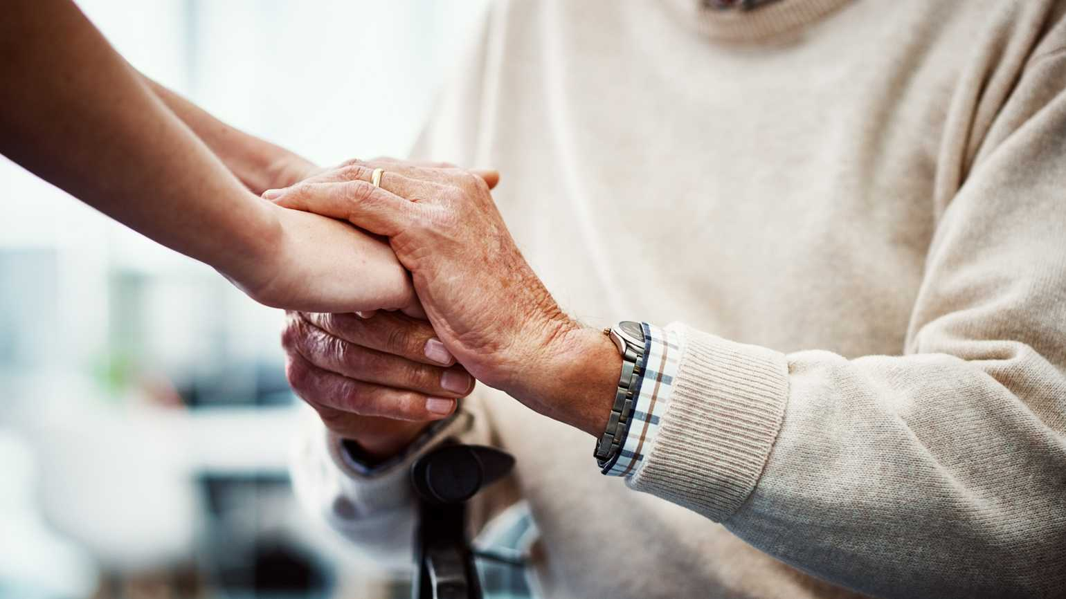 Cropped shot of an female nurse holding her senior patient's hand in comfort.