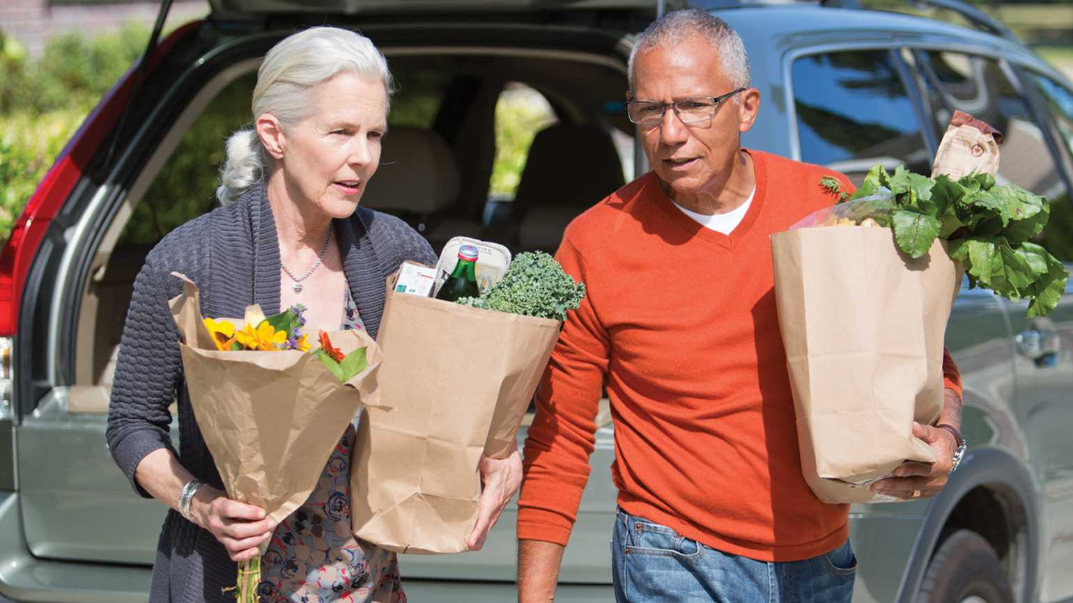 An elderly couple carrying bags of various groceries out of their car.