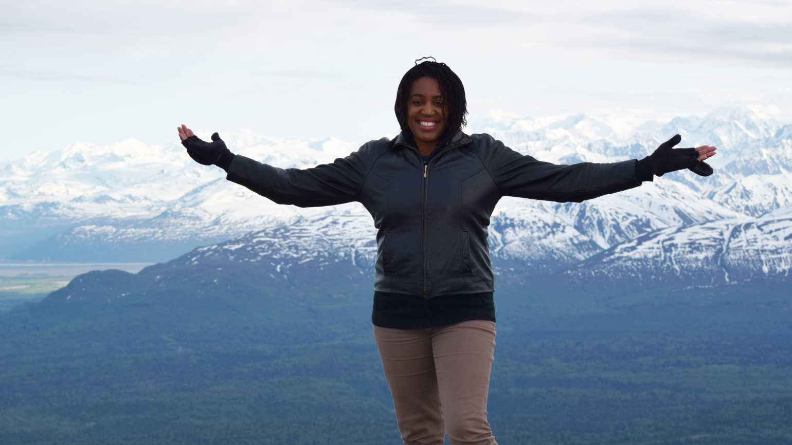 Guideposts senior digital editor Brooke Obie stands on top of an Alaskan mountain range