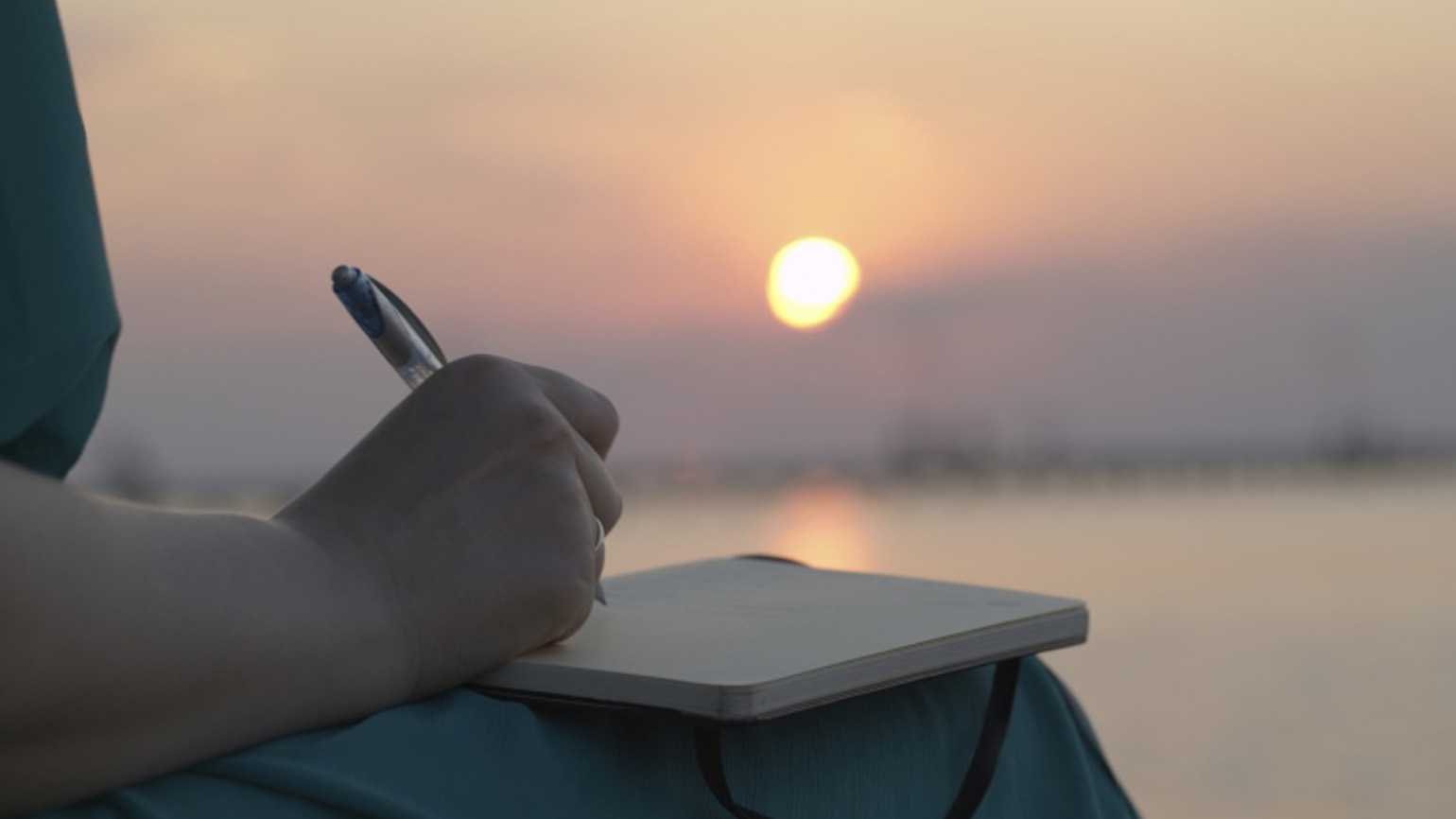 A woman journaling during sunset.