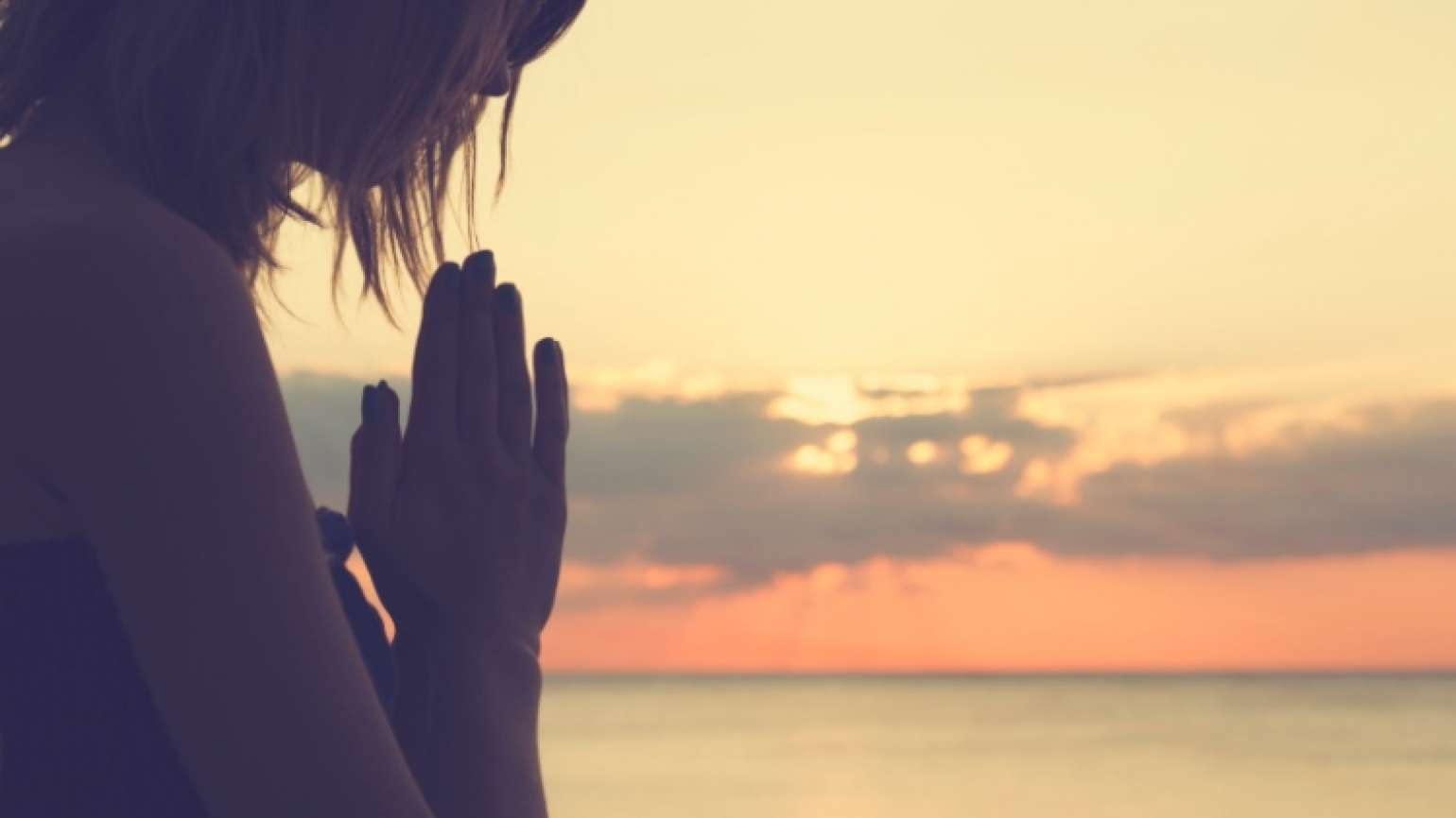 Woman praying at sunrise