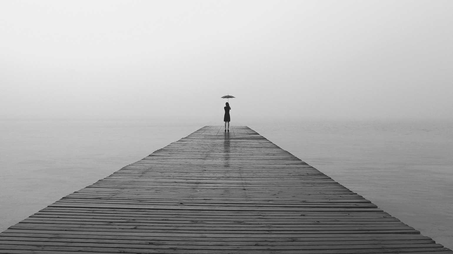 A woman stands at the end of a long, foggy pier, umbrella in hand