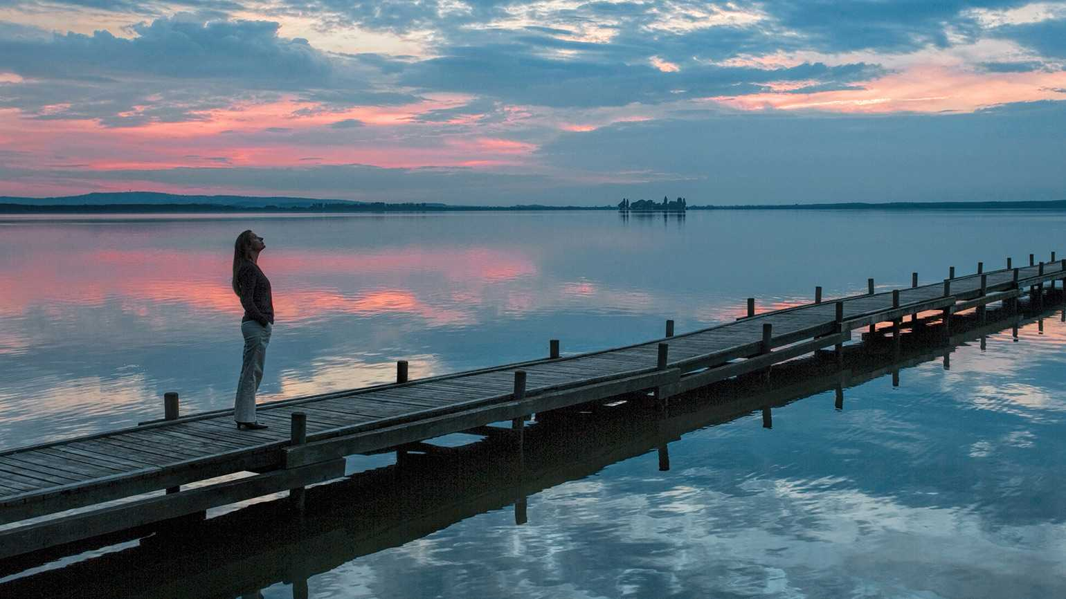 A woman gazes skyward at sunset while standing on a jetty extending into a lake
