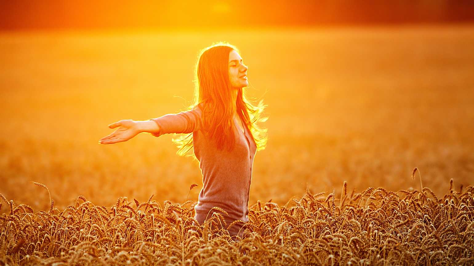 Woman with arms outstretched in sun-drenched wheat field
