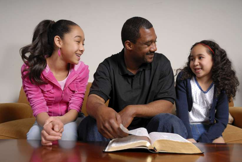 Daughters reading scripture to their dad on Father's Day