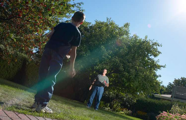 A father plays catch with his son in the back yard.