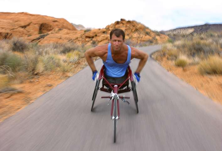 A man in a racing wheelchair sprints along a desert road.
