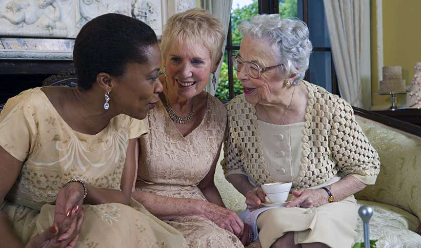 Three mature woman converse over coffee.