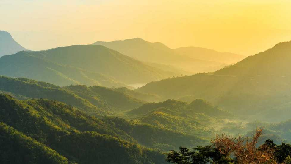 Lush mountain view with sun rising; Getty Images
