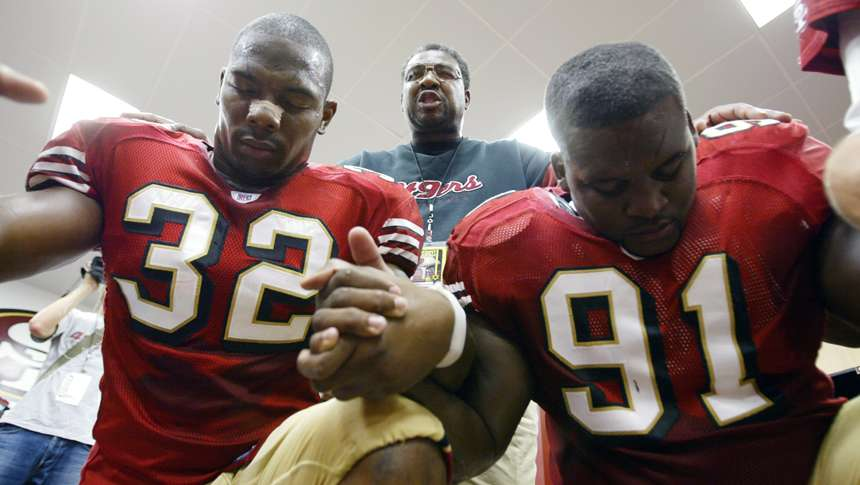 Smith prays with Kevan Barlow (left) and Anthony Adams in the locker room before a 2005 home game against the Indianapolis Colts.