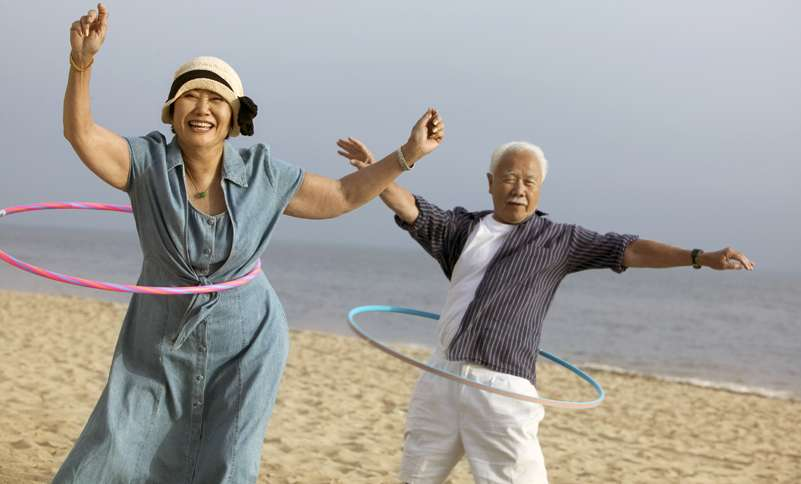 A woman and her father laugh as they hula hoop on the beach.