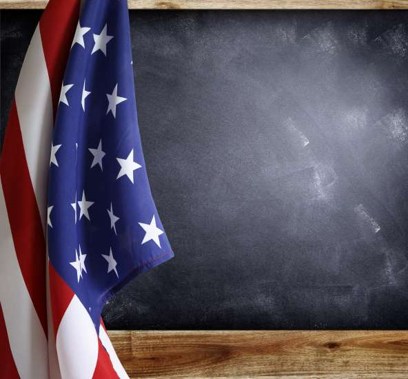 American flag hanging from a school room chalkboard