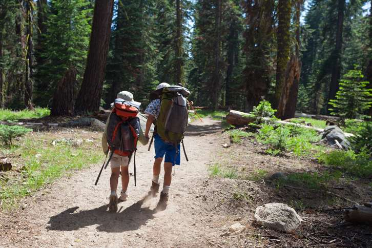 Guideposts: Parent and child hold hands as they hike in the woods.