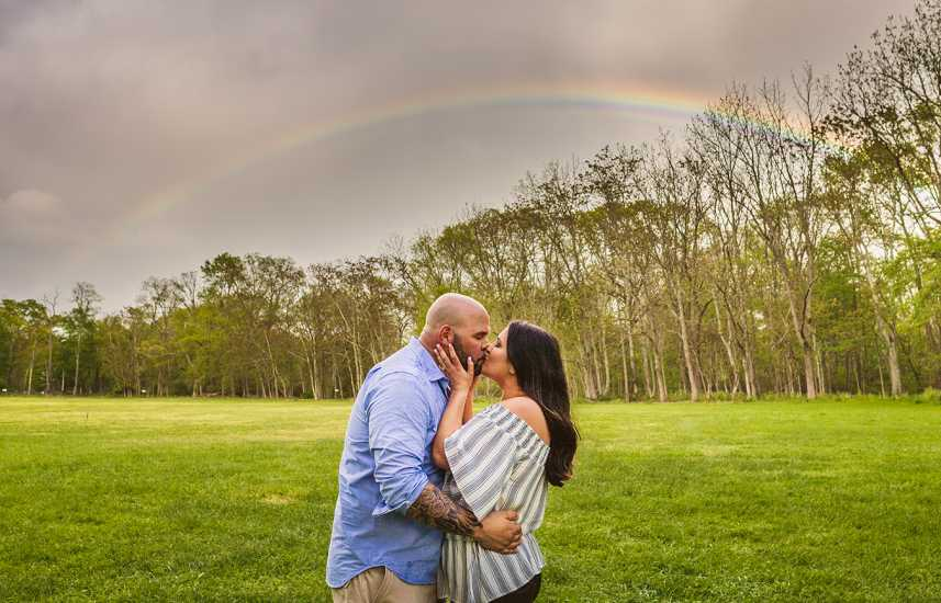 John and Courtney kiss in front of the heavenly rainbow