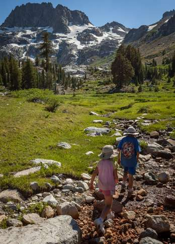 Guideposts: Rebekah and Cade across an open meadow with snow-capped mountains in the distance