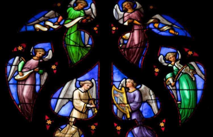 Stained glass detail of angels playing instruments.