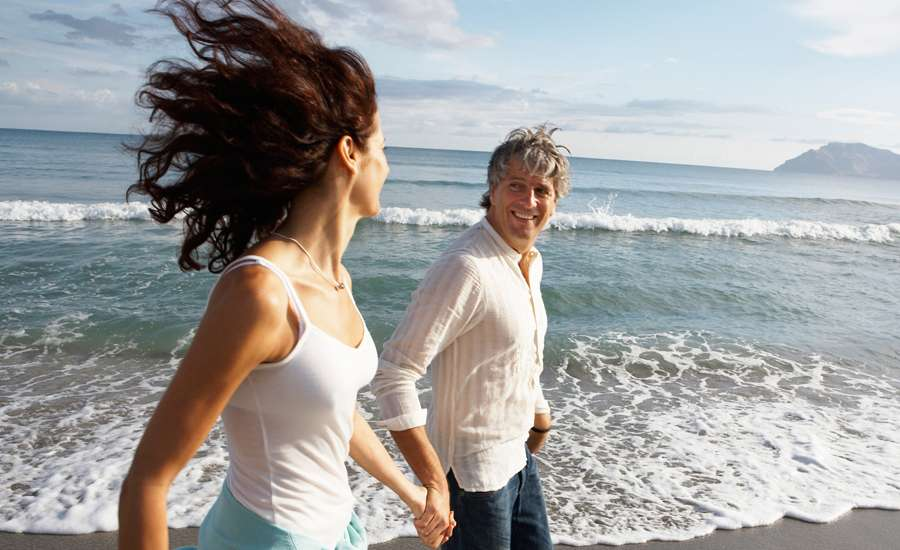 man and woman walk along the beach holding hands