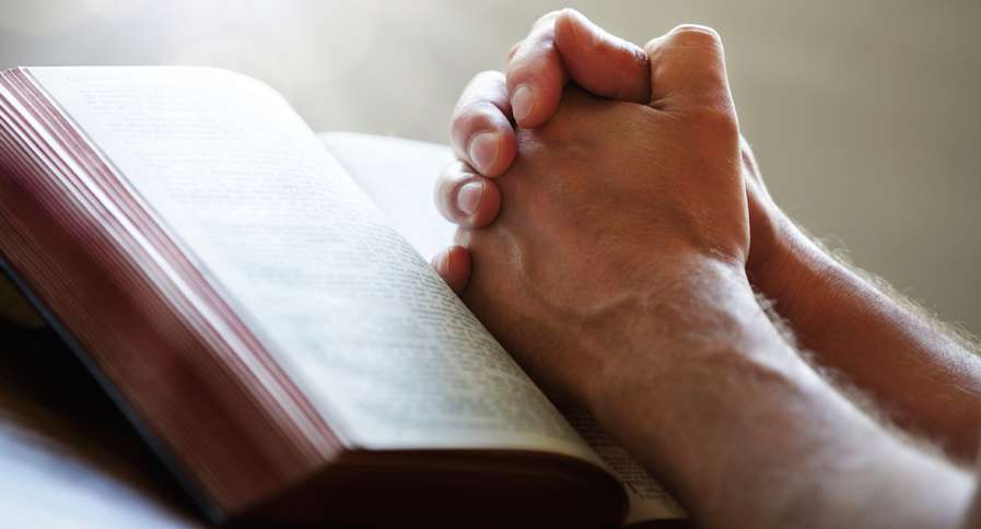 A man's praying hands rest upon an open Bible.