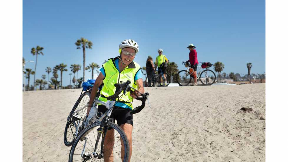 Dog Beach, San Diego – Carol Garsee, Cancer survivor, running with her bike to dip her wheels in the Pacific Ocean. better living health wellness living longer living better