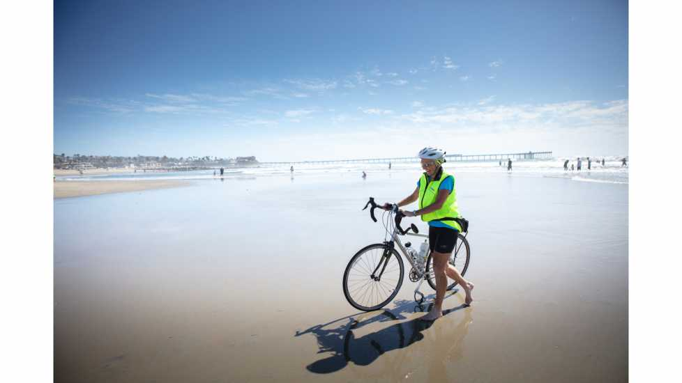 Carol Garsee, Cancer survivor, at Dog Beach, San Diego – All finished her cross country bike ride to the Pacific Ocean.  better living health wellness living longer living better