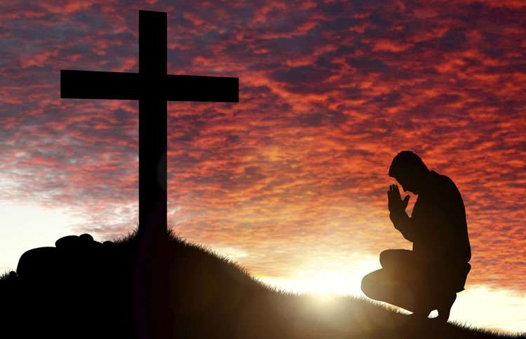 A man kneels at the foot of a cross on a hill at sunset