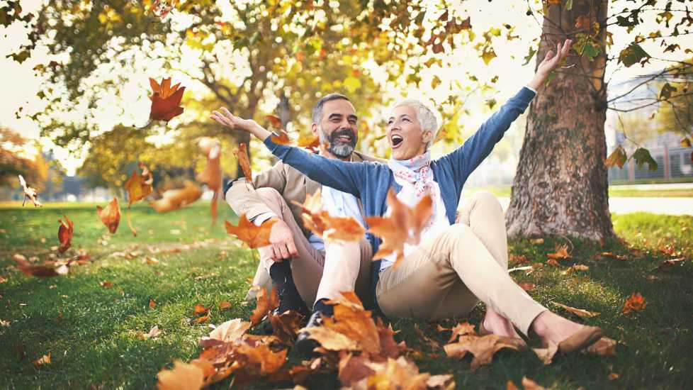 Couple in park enjoying autumn leaves (Getty)