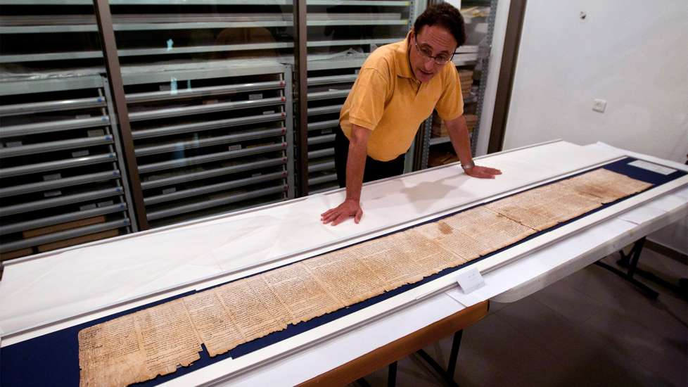 A researcher looks over a scroll fragment