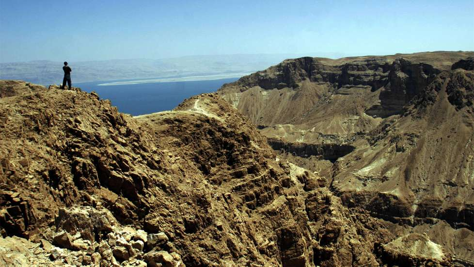 A lone figure stands upon the jagged rocks of Qumran and gazes out over the Dead Sea