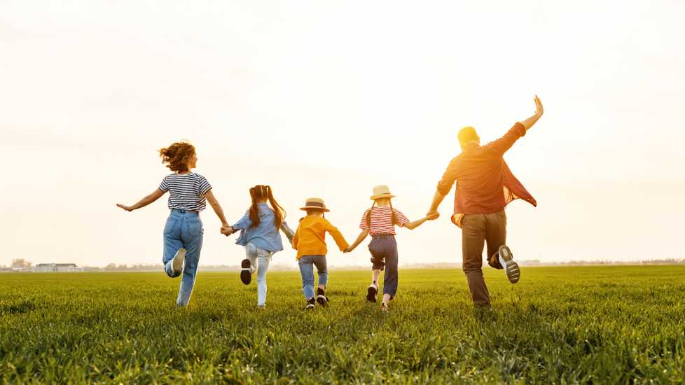 Family running through green field (Getty Images)