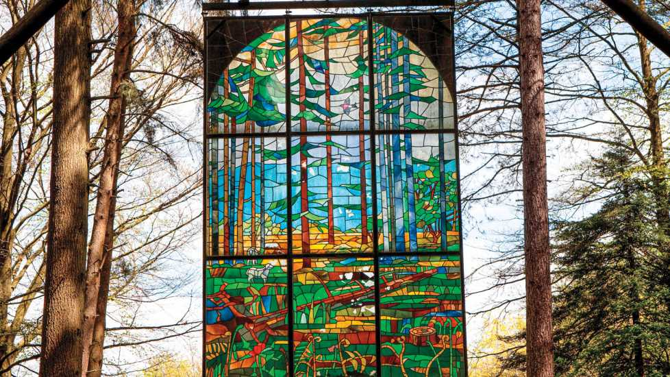 Cathedral' by Kevin Atherton, is a suspended stained glass panel in the Gloucestershire Forest of Dean Sculpture Park. Credit: Neil McAllister/Alamy