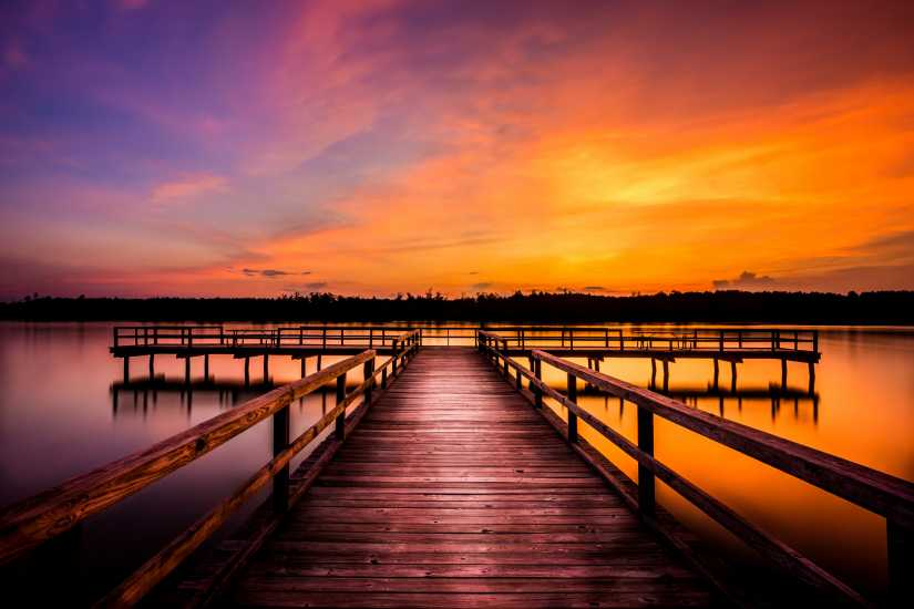 A dock overlooking a sunset over water; Getty Images