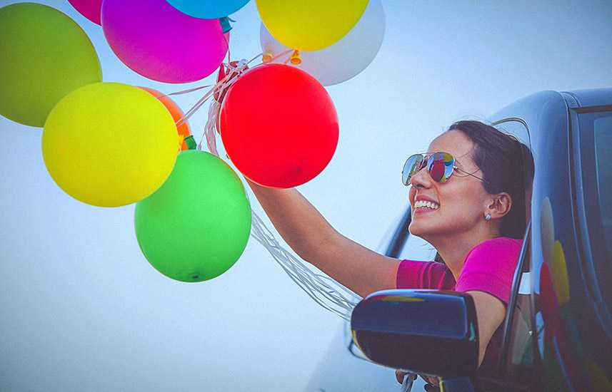 Cheerful woman holding balloons out of a car window